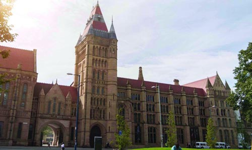 The gothic building of The University of Manchester, an impressive yellow brick and red tiled building.