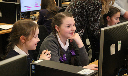 Two female students smiling at computer screen