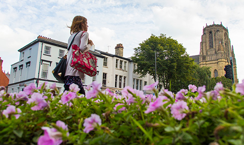 A woman walking next to flowers and the University