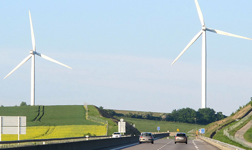 Wind turbines in a field overlooking a dual carriageway