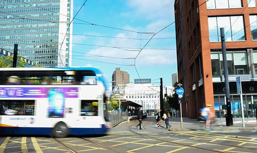 Buses going across tram lines in Piccadilly Gardens, Manchester