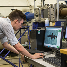 Researcher operating MACE wind tunnel computer equipment