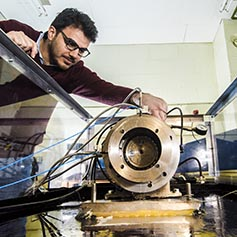 Researcher operating a vibration test rig