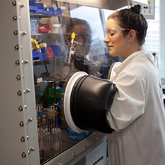 Researcher in white lab coat conducting experiment in machine