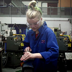 Student in blue lab coat working on machine in workshop