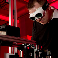 Researcher using laser equipment wearing dark safety goggles