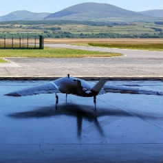 Military aeroplane in hangar looking out at fields and mountains