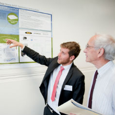Two men looking at a chart on a wall