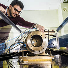Researcher monitoring equipment in the dynamics lab