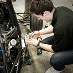Student adjusting timer device while knelt next to go-kart