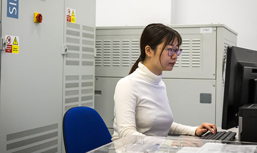 Female engineer sits at a computer.
