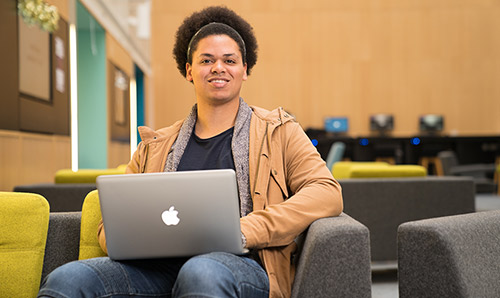 A male student smiles at the camera from behind his laptop.